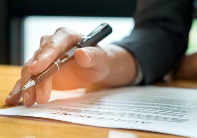 Businessmen holding pens in hand reading documents on the desk,B